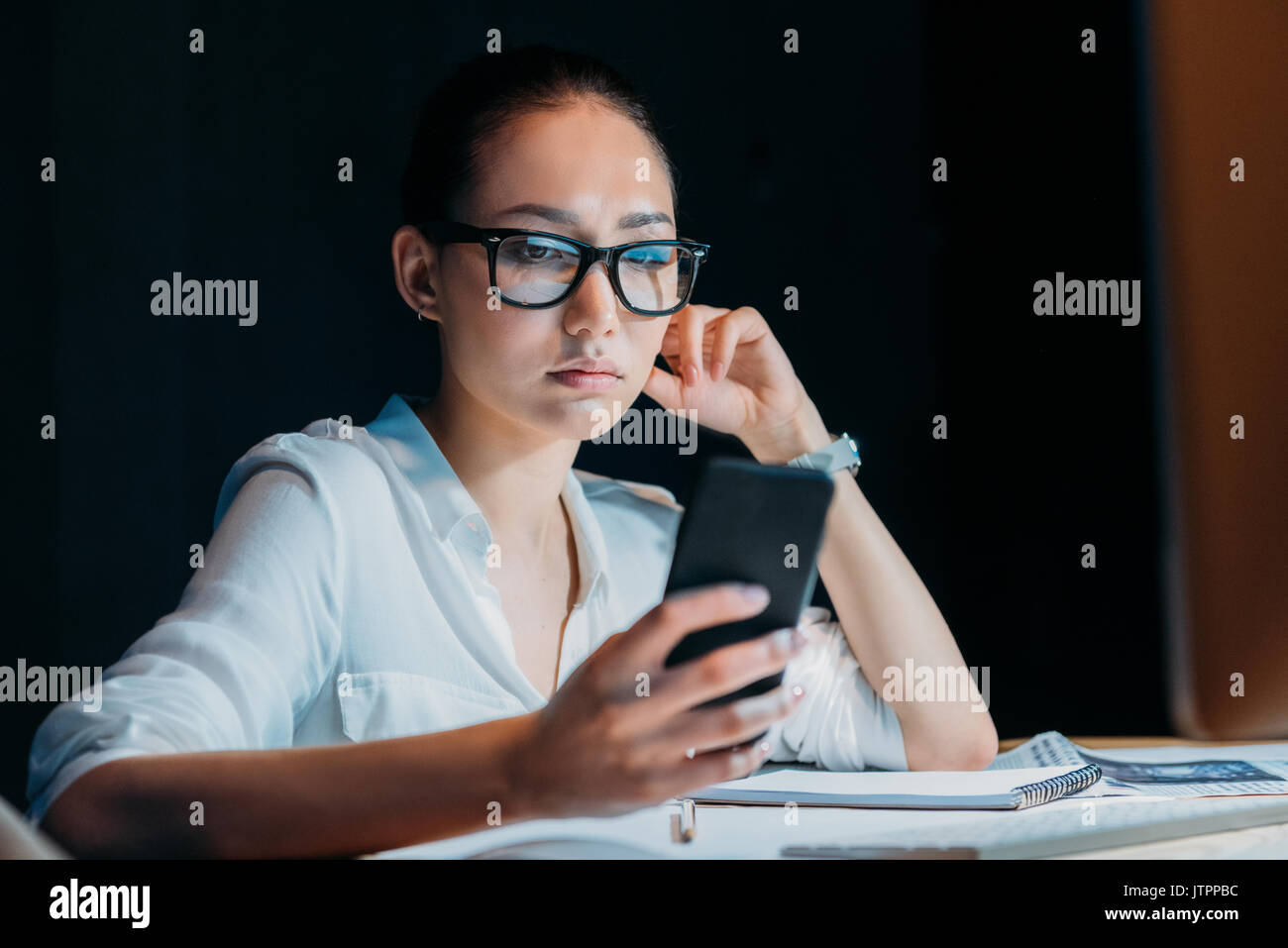 young tired asian businesswoman in eyeglasses using smartphone and working till late in office - Stock Image