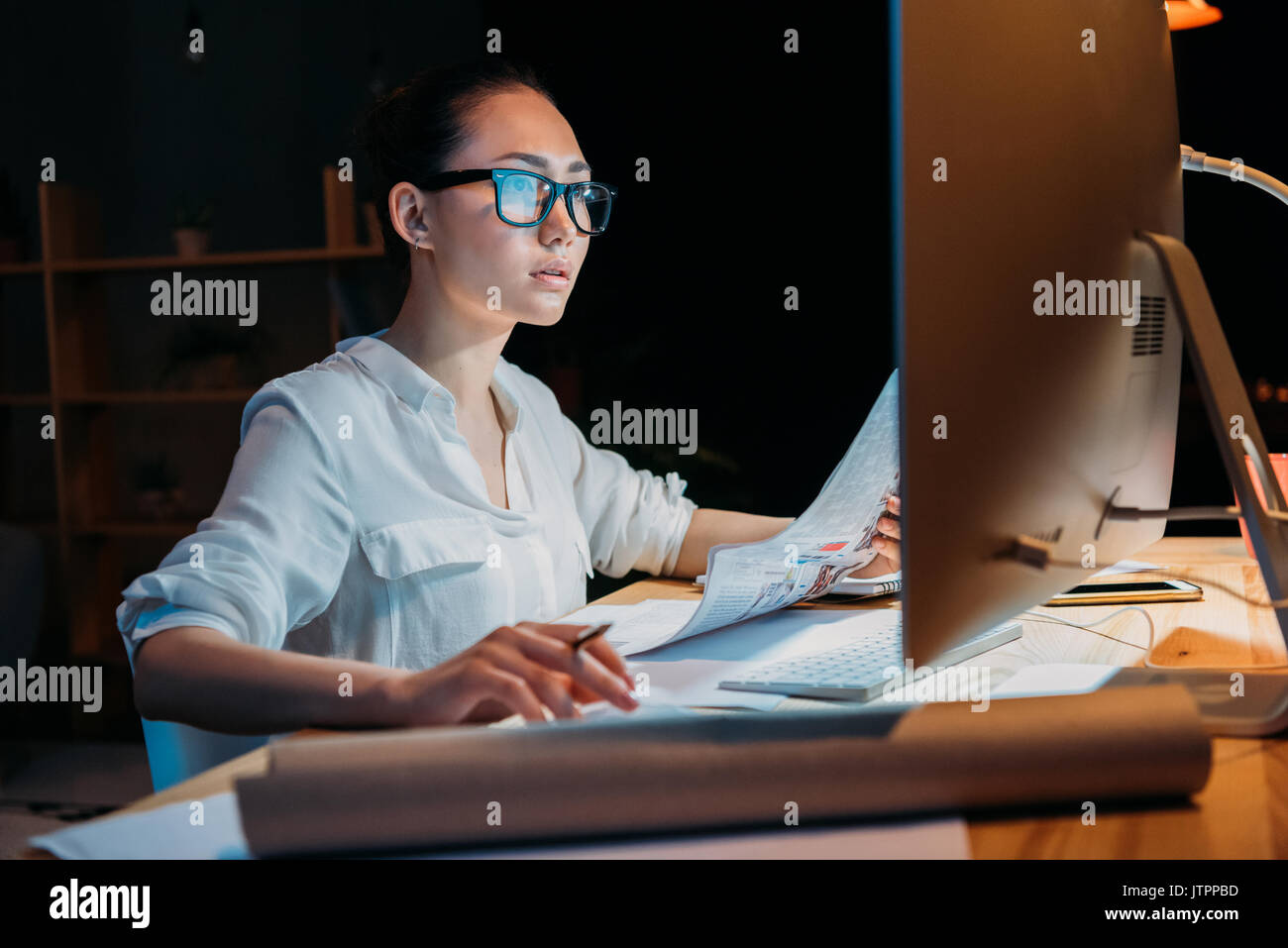 young concentrated asian businesswoman in eyeglasses working with documents and computer - Stock Image