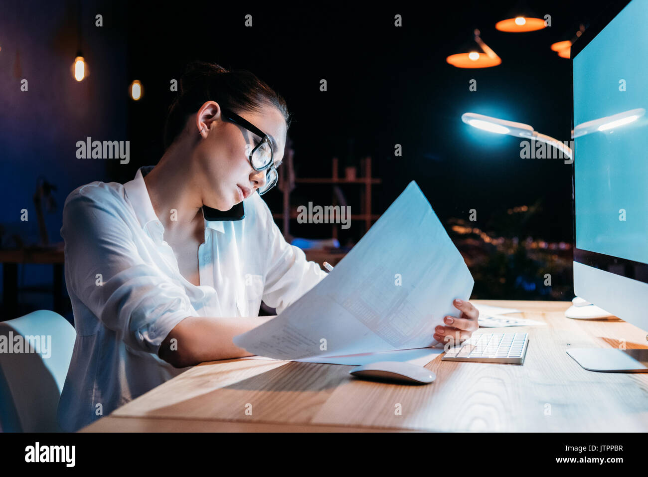 Young asian businesswoman in eyeglasses holding blueprint and talking on smartphone  Stock Photo