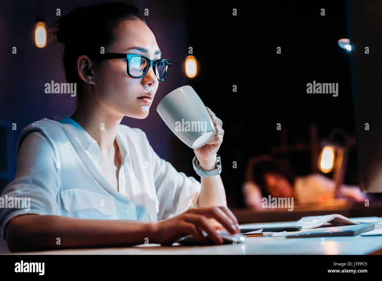 Young businesswoman in eyeglasses holding cup while working late in office  - Stock Image