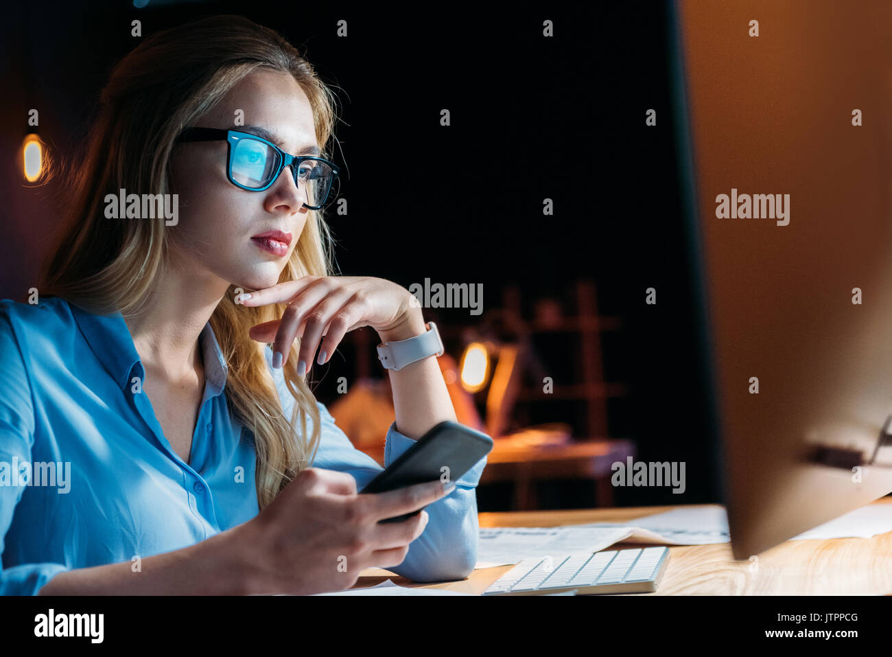 portrait of businesswoman using smartphone while working late in office - Stock Image