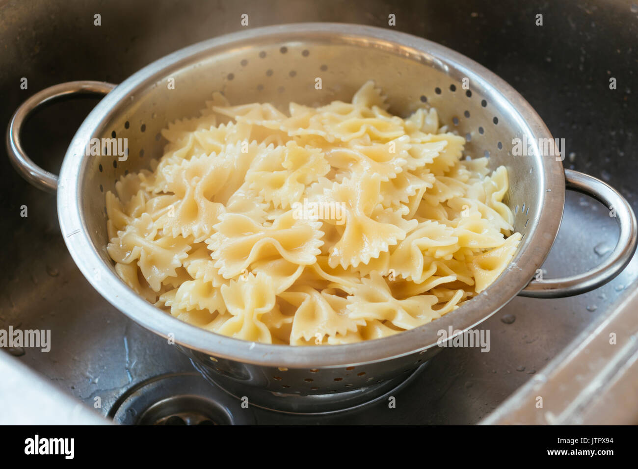 Cooked farfalle (bow-tie) pasta in a colander - Stock Image