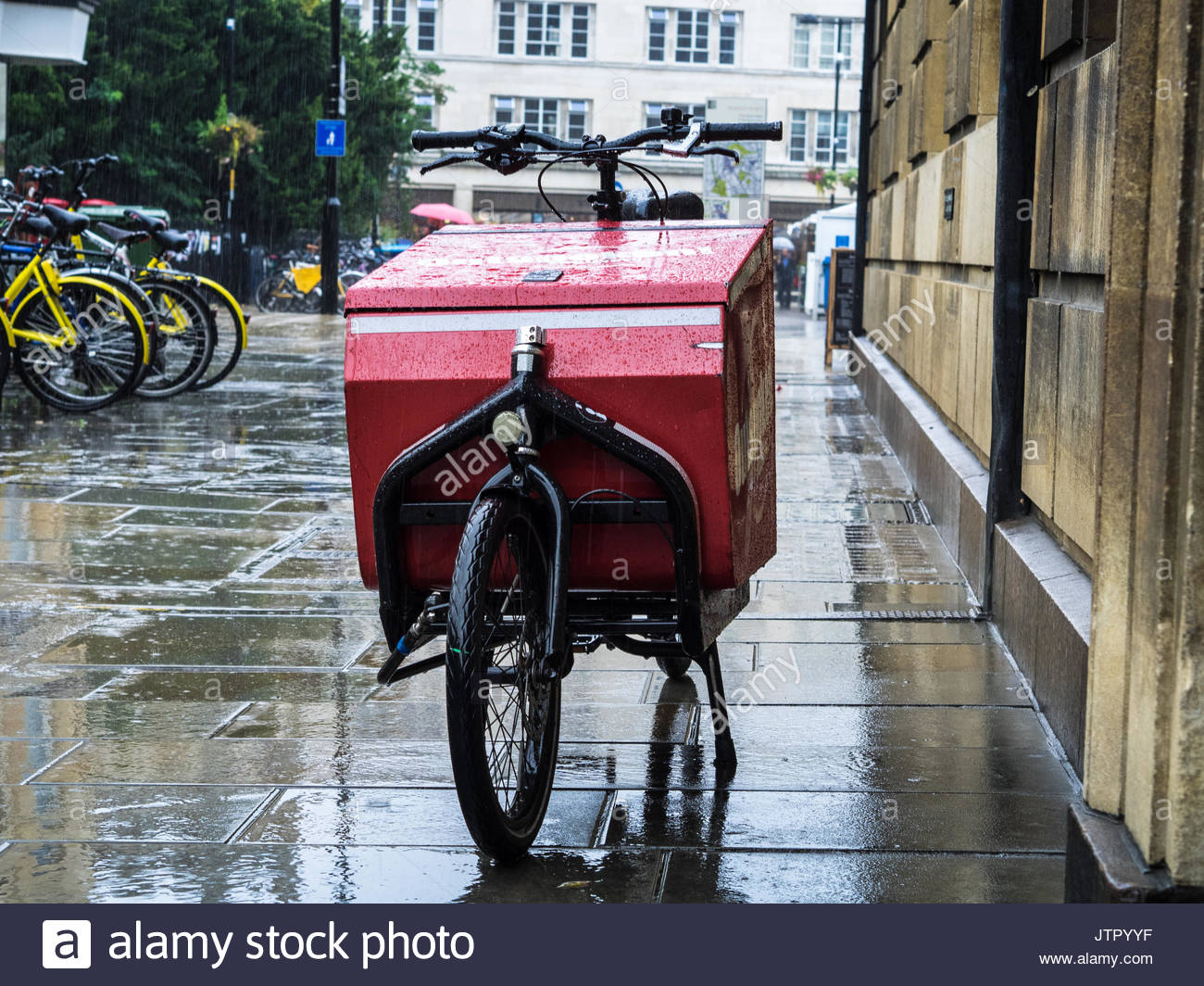 Cargo Bike Delivery - Cargo bike from the Outspoken last mile logistics company sits in the rain in Cambridge UK - Stock Image
