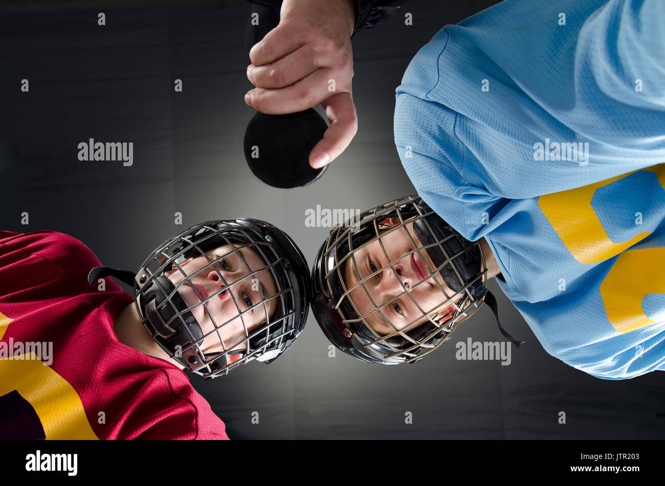 Cloesup of a hockey faceoff with teenage hockey players and puck - Stock Image