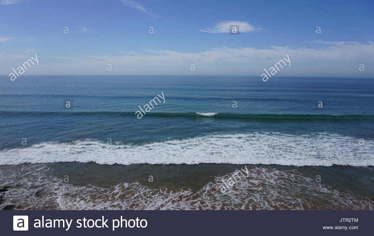 Tiny waves breaking in Taghazout Morocco - Stock Image