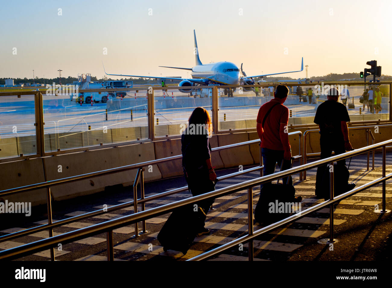 Passengers boarding airplane at an airport at sunset - Stock Image