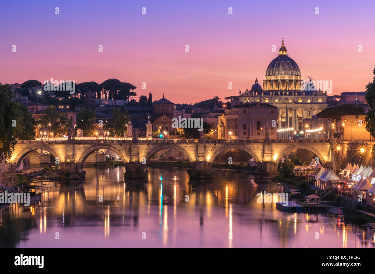 View of a stunning sunset setting behind the Vatican City from Ponte Umberto I, Rome, Italy - Stock Image