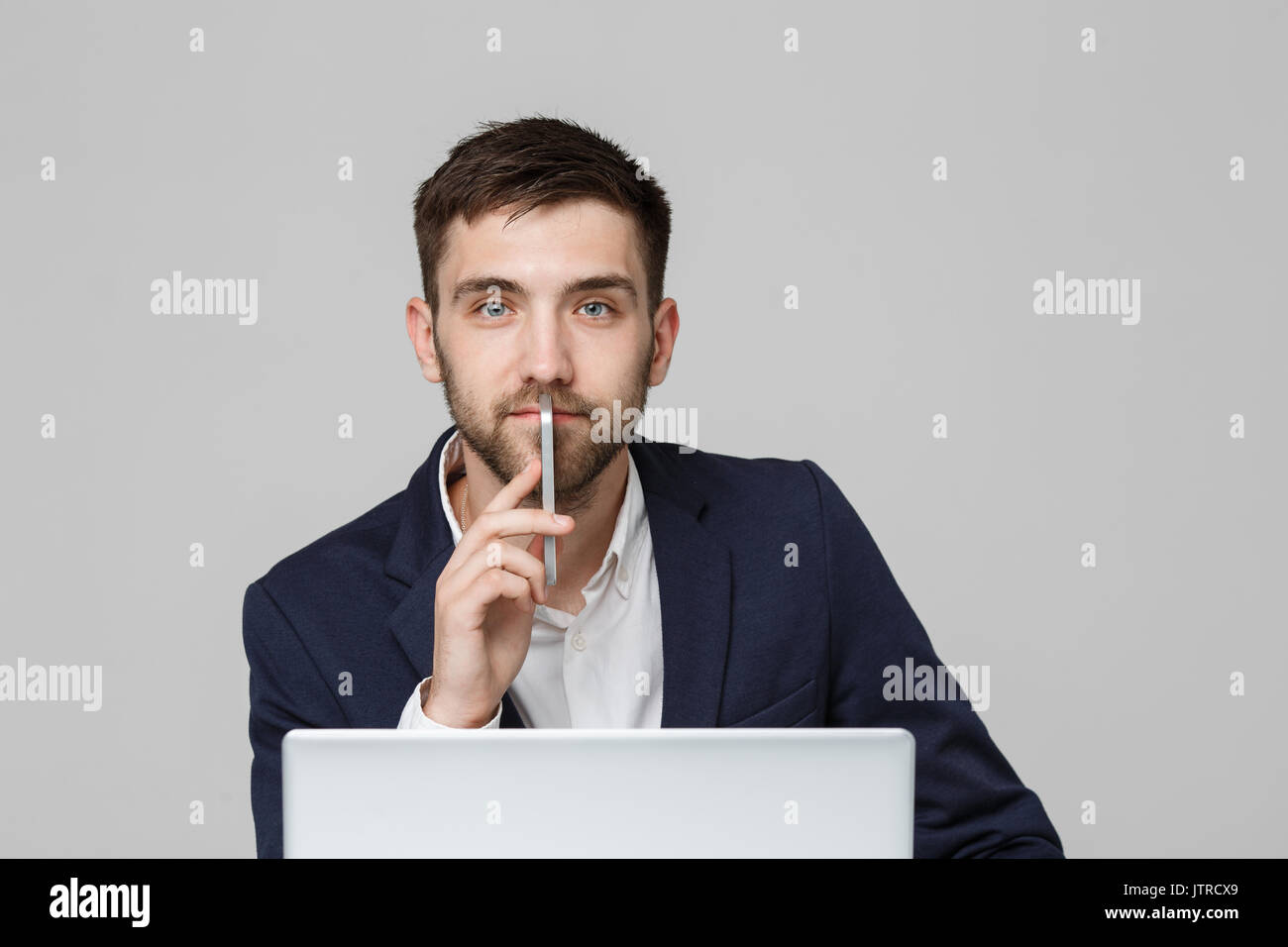 Business Concept - Portrait handsome happy handsome business man in suit playing moblie phone and smiling with laptop Stock Photo