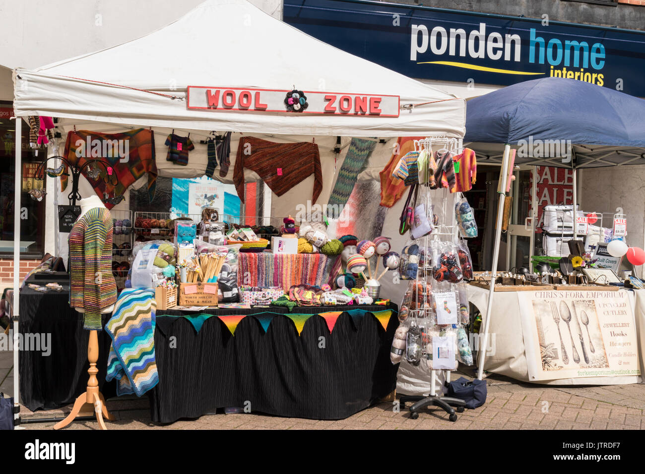 Melton Mowbray folk festival and craft fair,wool stall selling all shades and colourful woollen item. Ponden home interiors shop in the background. - Stock Image