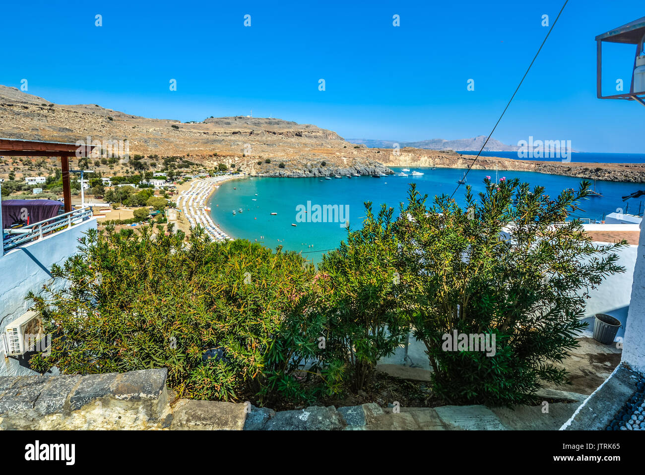 Small bay at Lindos on the island of Rhodes Greece crowded with beach umbrellas as boats and swimmers enjoy the bay and Mediterranean Sea on a hot day - Stock Image