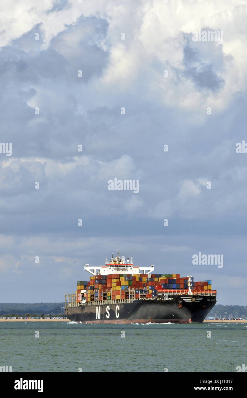 a large container ship leaving or entering Southampton docks imports and exports by sea and containerisation products ready for distribution by rail - Stock Image