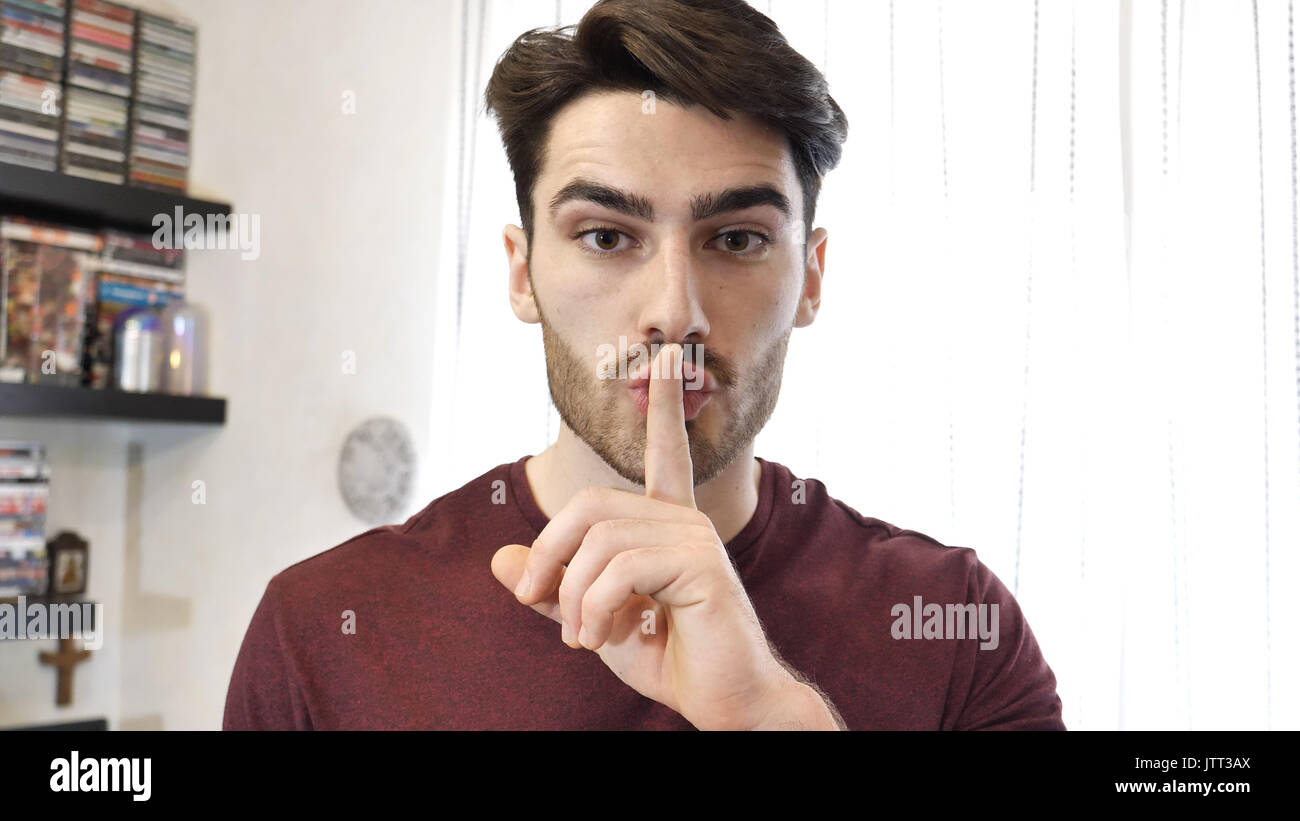 Handsome young man doing Hush sign with finger on lips - Stock Image