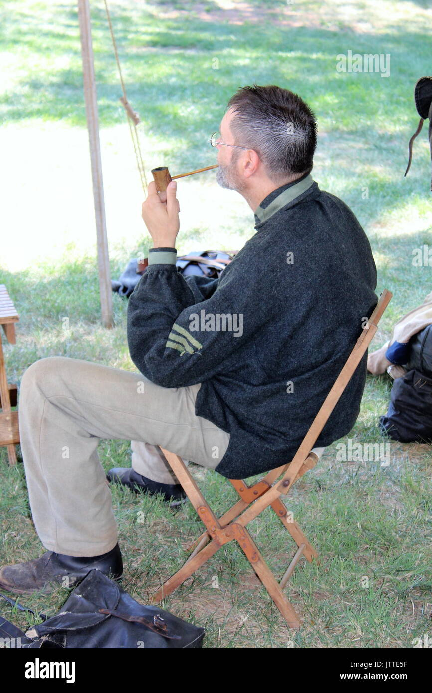 Re-enactor portraying a Confederate enlisted soldier who is enjoying a moment of pipe smoking - Stock Image
