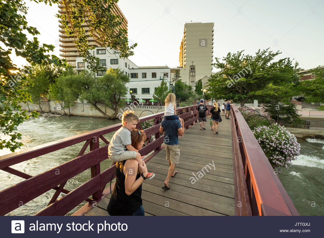 People walking on pedestrian bridge spanning the Truckee River near Wingfield Park, Reno, Washoe County, Nevada, USA - Stock Image