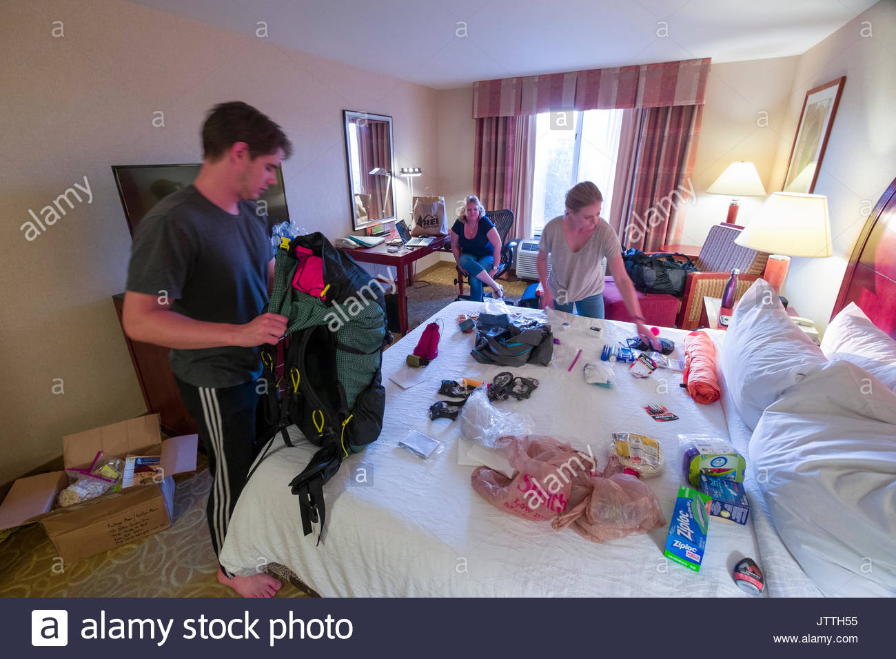 Young man and woman sorting backpacking gear on bed in hotel room before embarking on a five month journey hiking the Pacific Crest Trail, USA - Stock Image