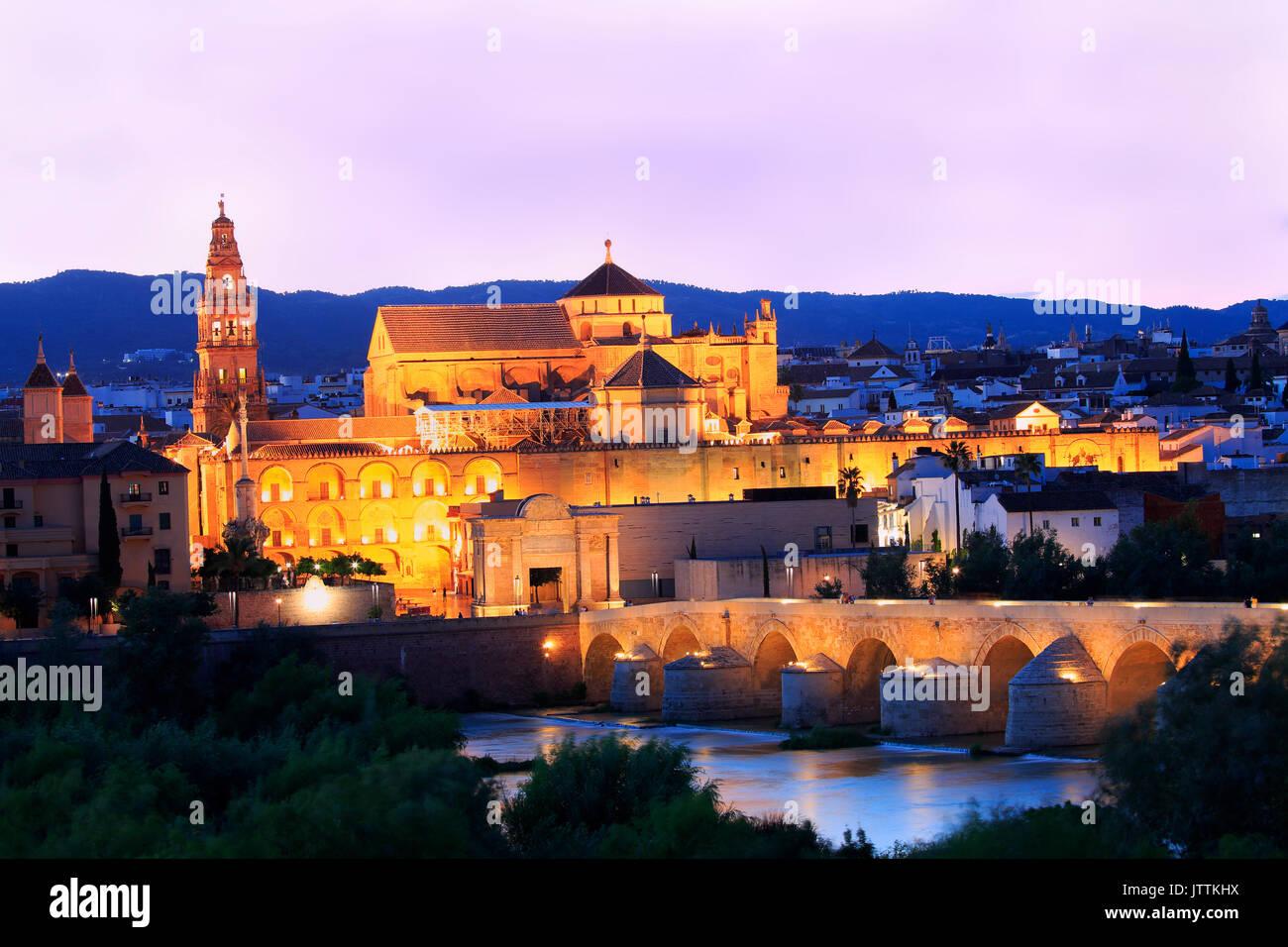 Roman Bridge and Guadalquivir River illuminated at dusk, Great Mosque in Cordoba, Spain - Stock Image