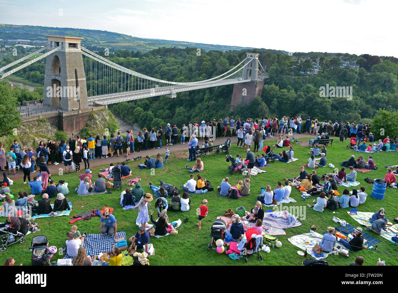 Bristol, UK. 10th Aug, 2017. UK Bristol. Thousands of people sitting on the grass by the observatory tower over looking World famous Clifton Suspension Bridge, hoping to get a wonderful view of the balloons as they lift off from Ashton Court Estate on the first evening of the Event. Mandatory Byline Credit: Robert Timoney/Alamy Live News - Stock Image