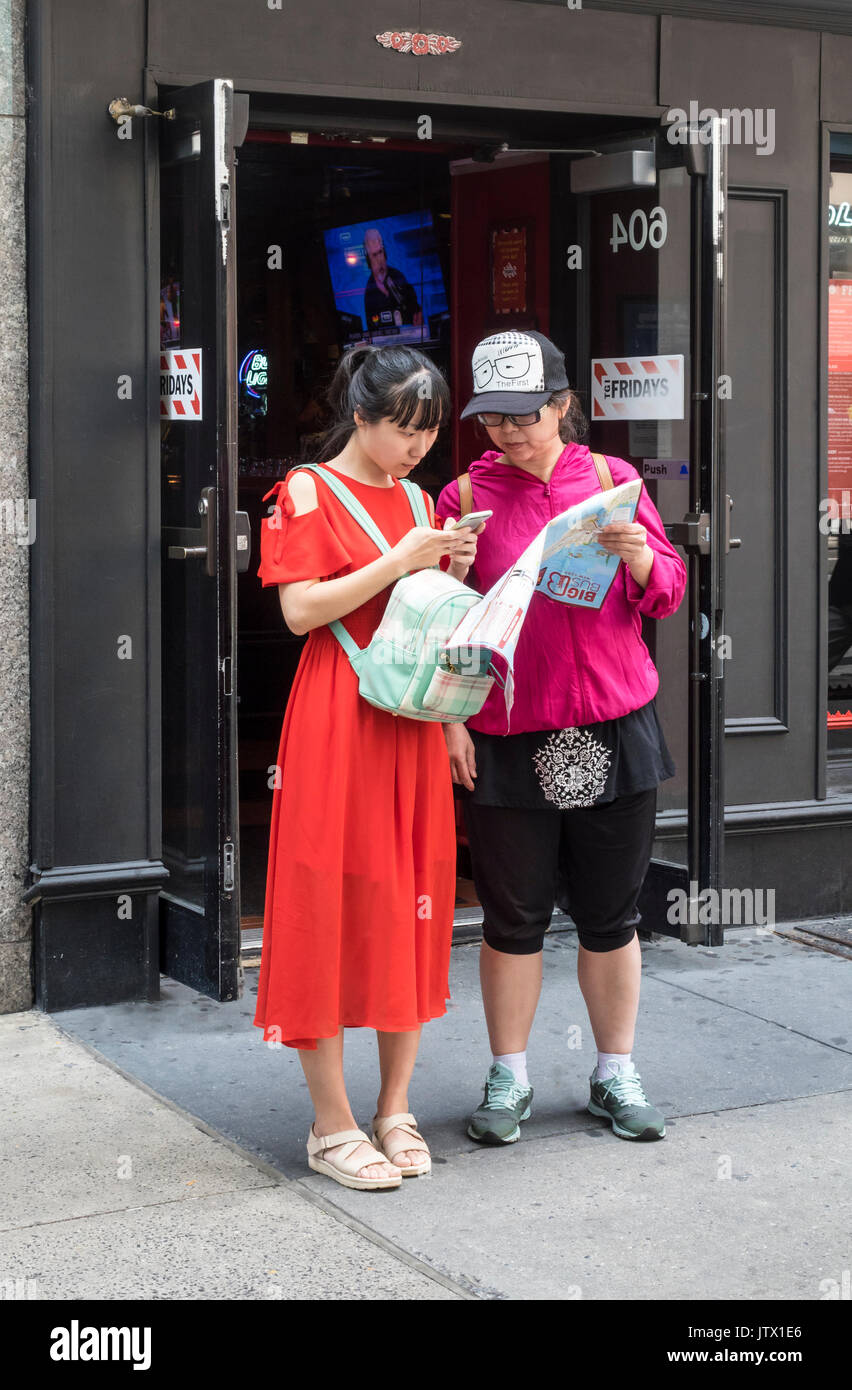 Two female Asian tourists consulting a map and cellphone for directions - Stock Image