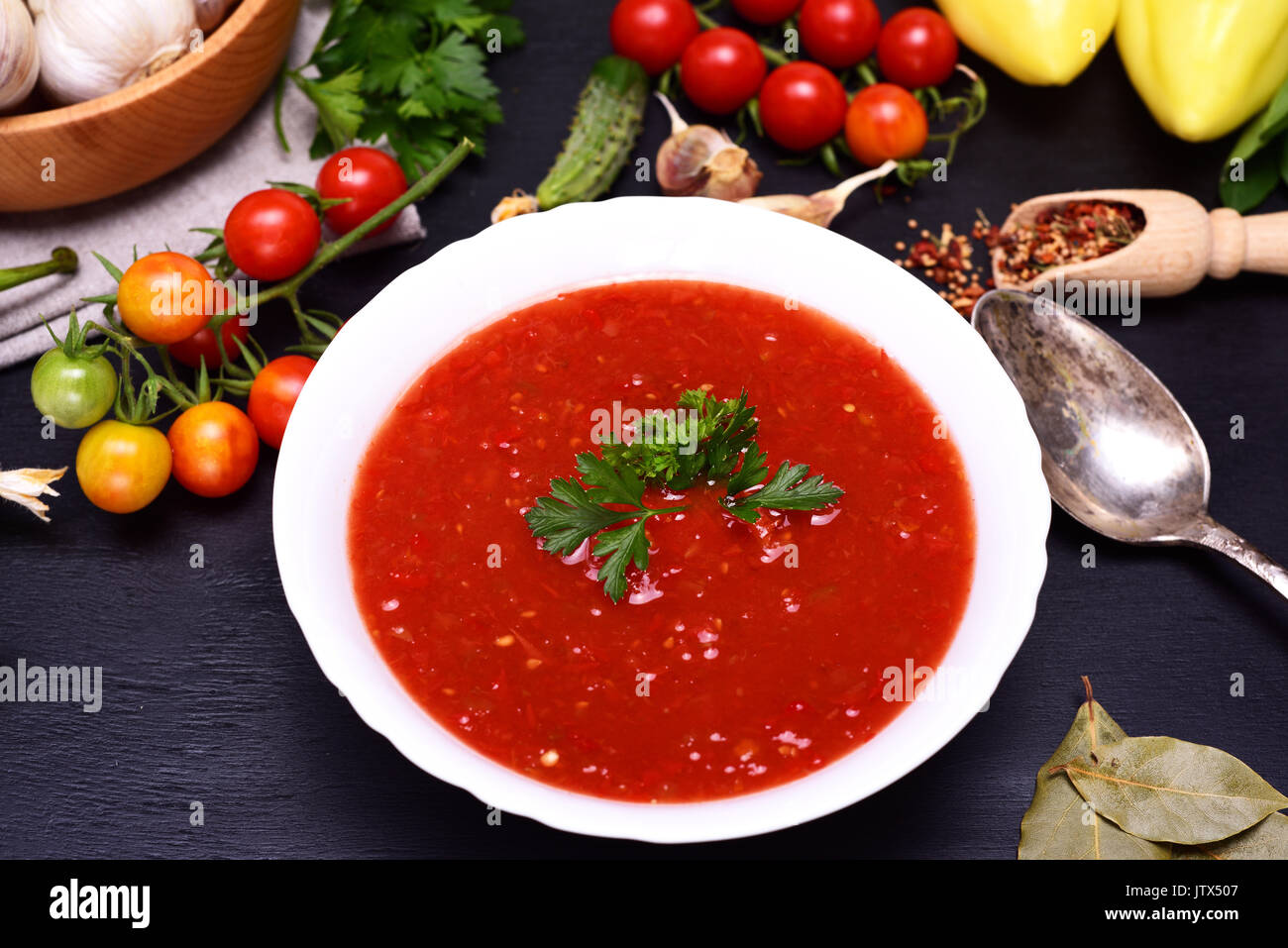 Gazpacho Spanish cold soup in a white round ceramic plate in the midst of fresh vegetables ingredients, top view - Stock Image