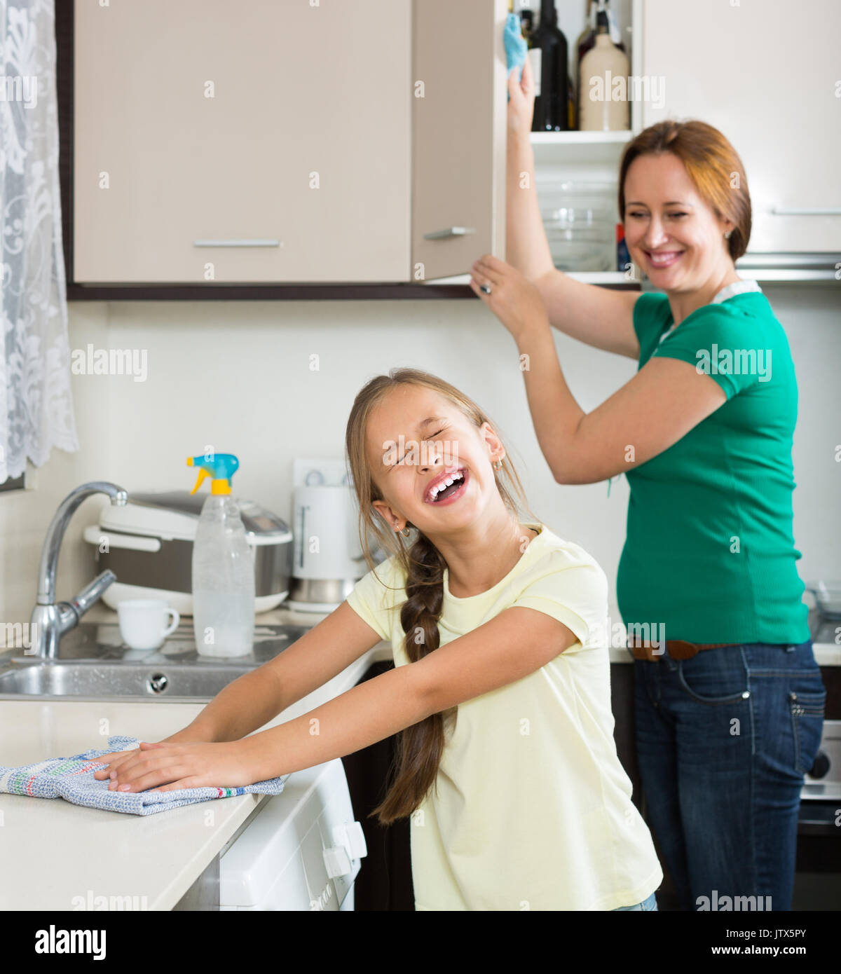 dusting furniture. Cheerful Girl Helping Mother Dusting Furniture Indoor. Focus On I