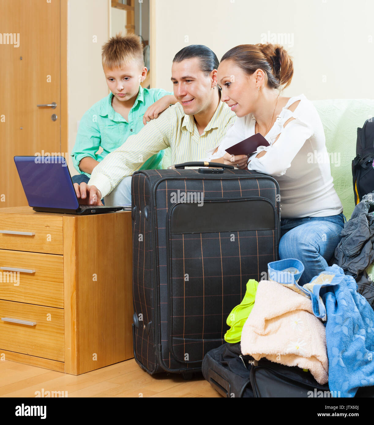 Ordinary family of three with luggage choosing the tickets in internet and going on holiday - Stock Image