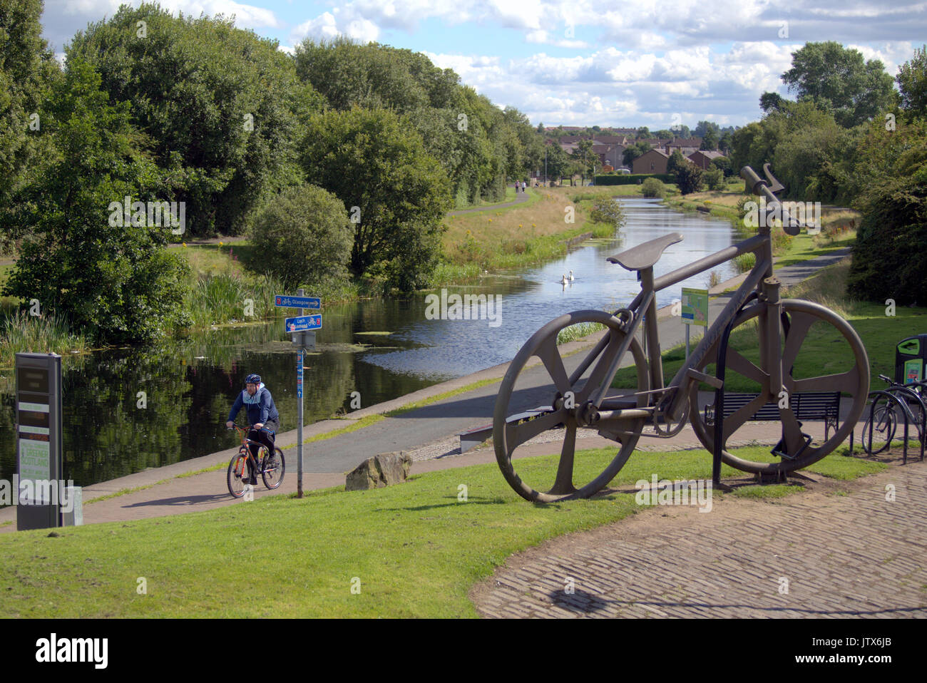 locals walking NCN 7 pass the Bankies bike sculpture at Clydebank  Summer weather and locals enjoy the summer  on the Forth and Clyde canal towpath - Stock Image