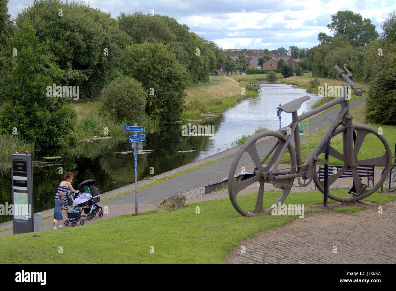 mother and child both pushing prams  pass the Bankies bike sculpture at Clydebank    in Summer weather on the Forth and Clyde canal towpath NCN 7 - Stock Image