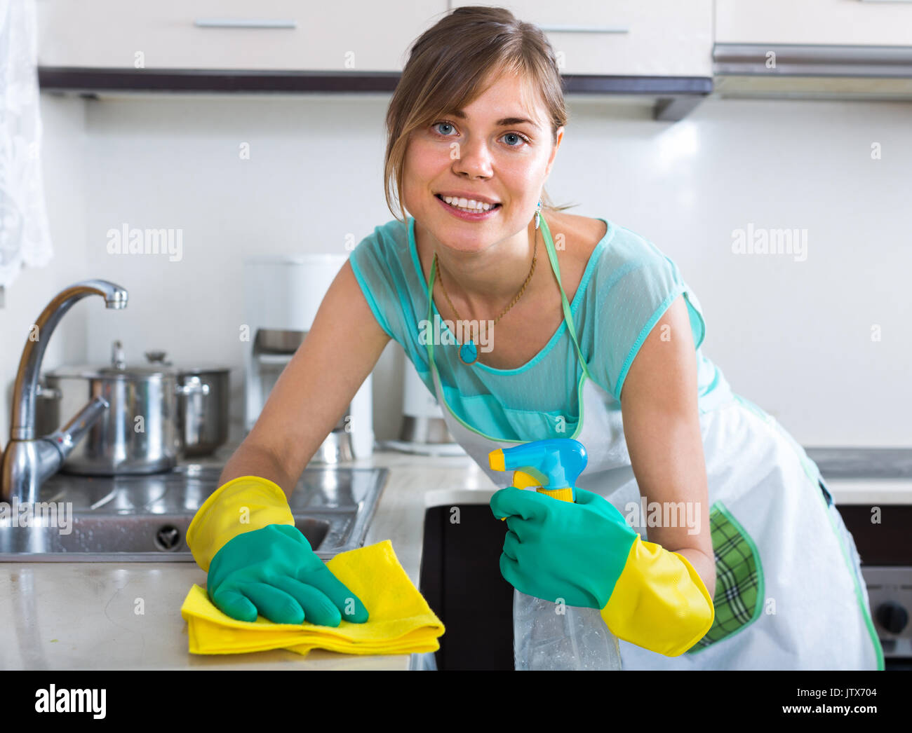 spanish maid doing professional clean-up in home kitchen Stock Photo ...