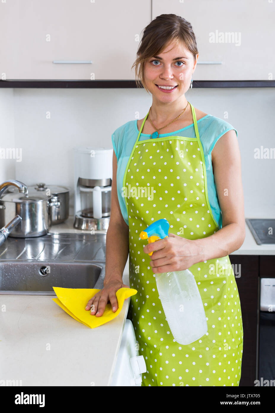 Smiling Maid Doing Professional Clean Up In Home Kitchen