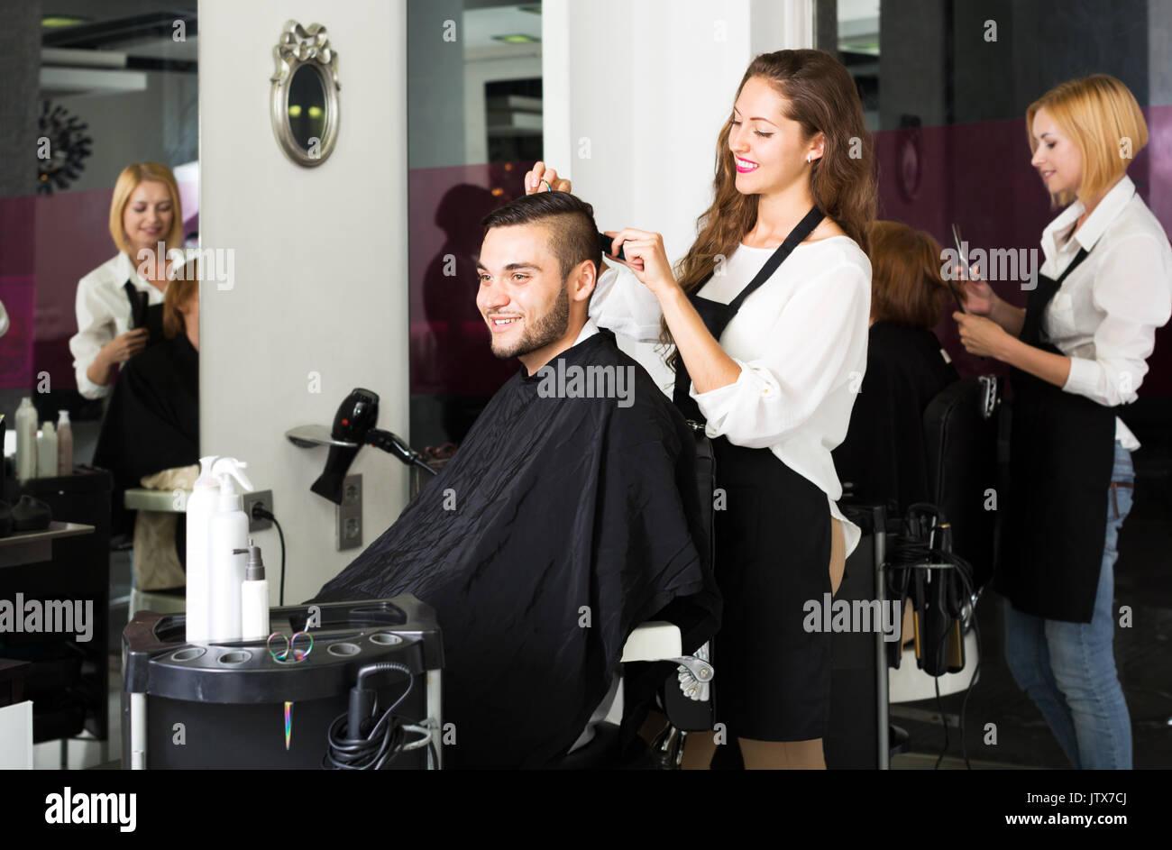 Happy guy cuts hair at the hair salon Stock Photo - Alamy