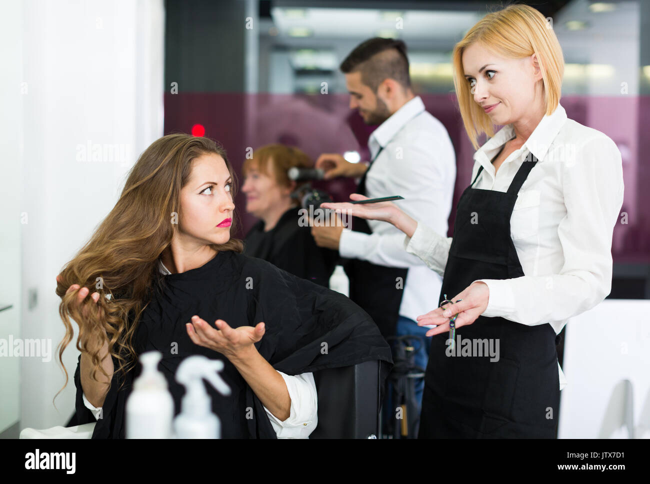 Serious sad young girl has a fight with barber - Stock Image