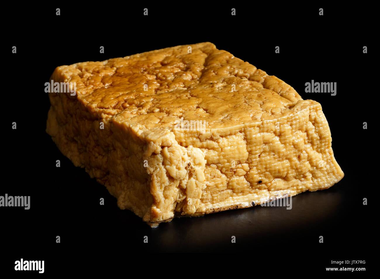 Single block of smoked tofu isolated on black. - Stock Image