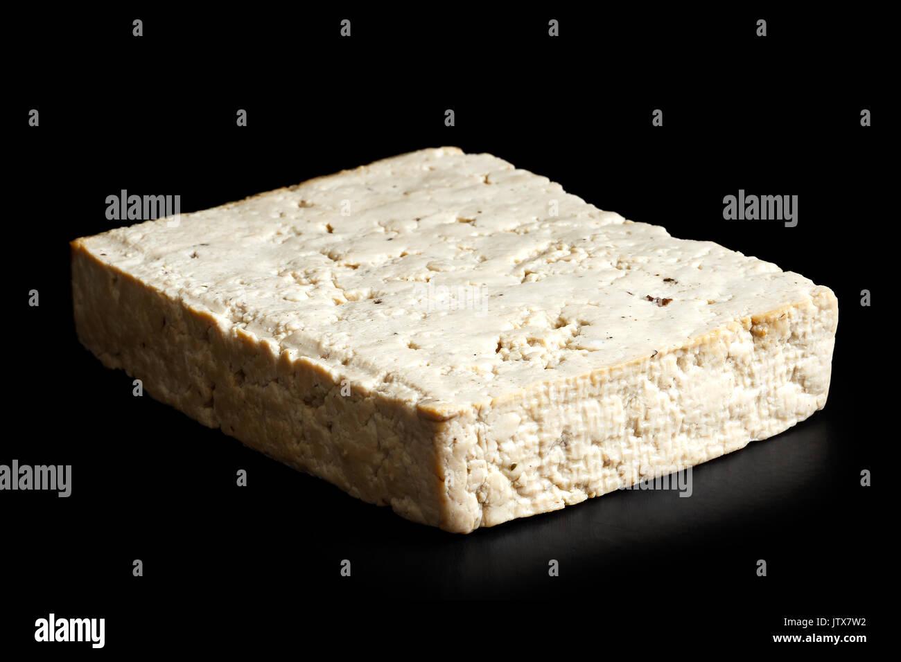 Single block of lightly smoked tofu isolated on black. - Stock Image