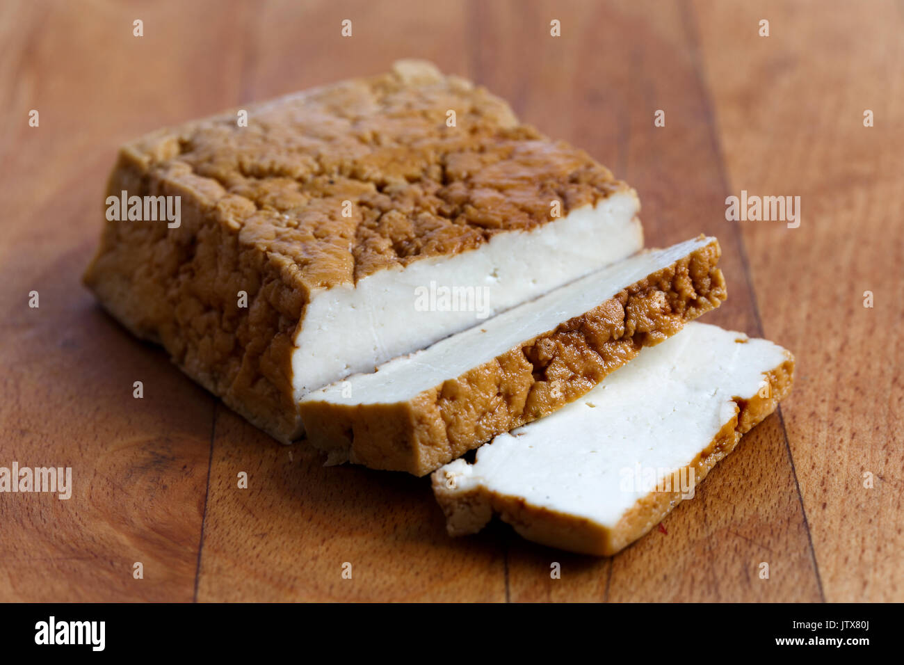 Block of smoked tofu and two tofu slices on wooden chopping board. - Stock Image