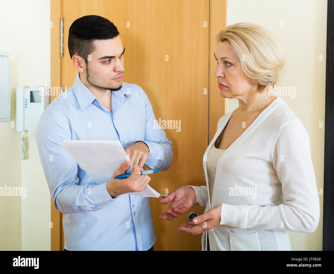 Сollector is trying to get the arrears from woman at home door - Stock Image