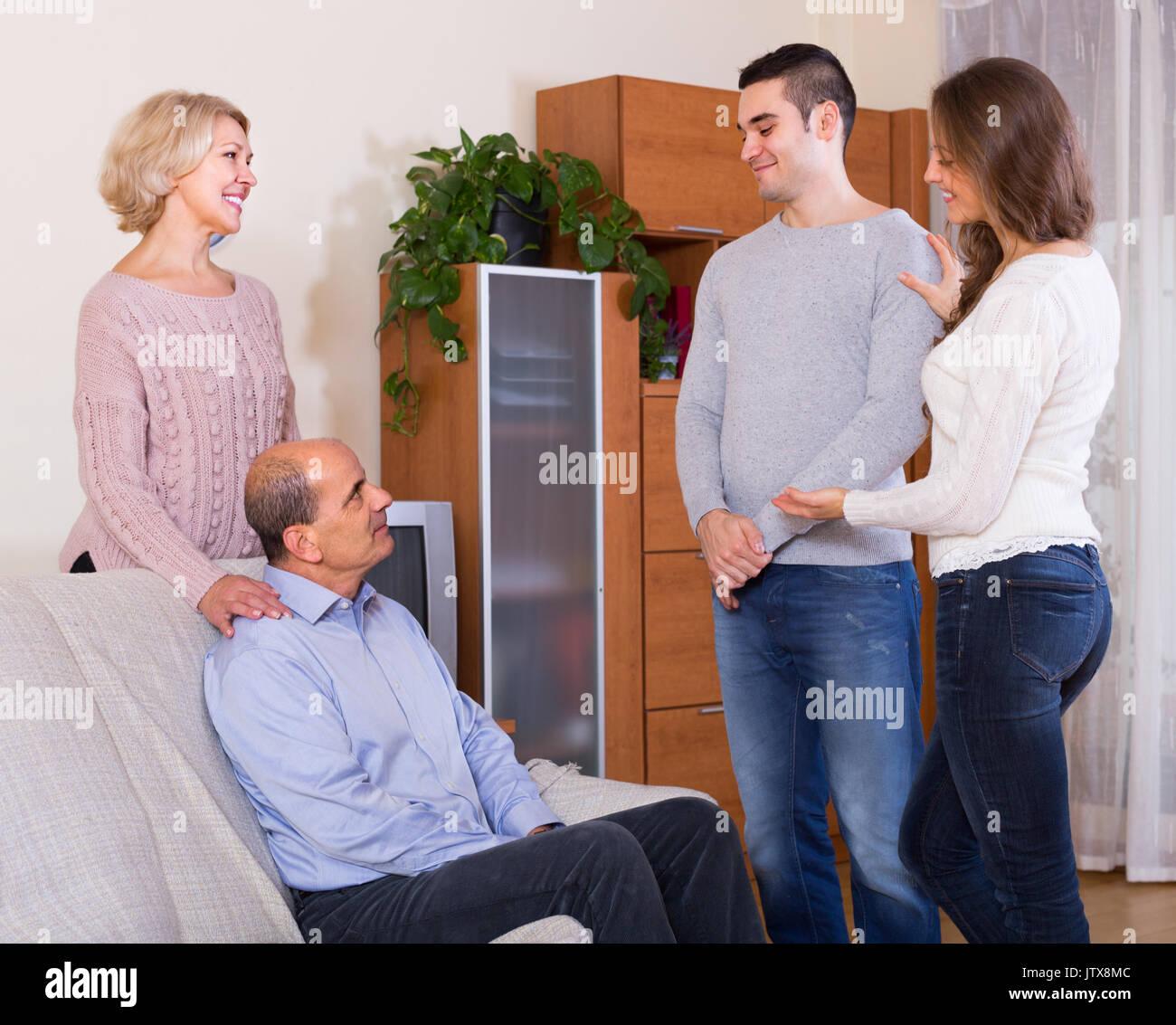 Happy adult daughter introducing her boyfriend to her parents indoor - Stock Image