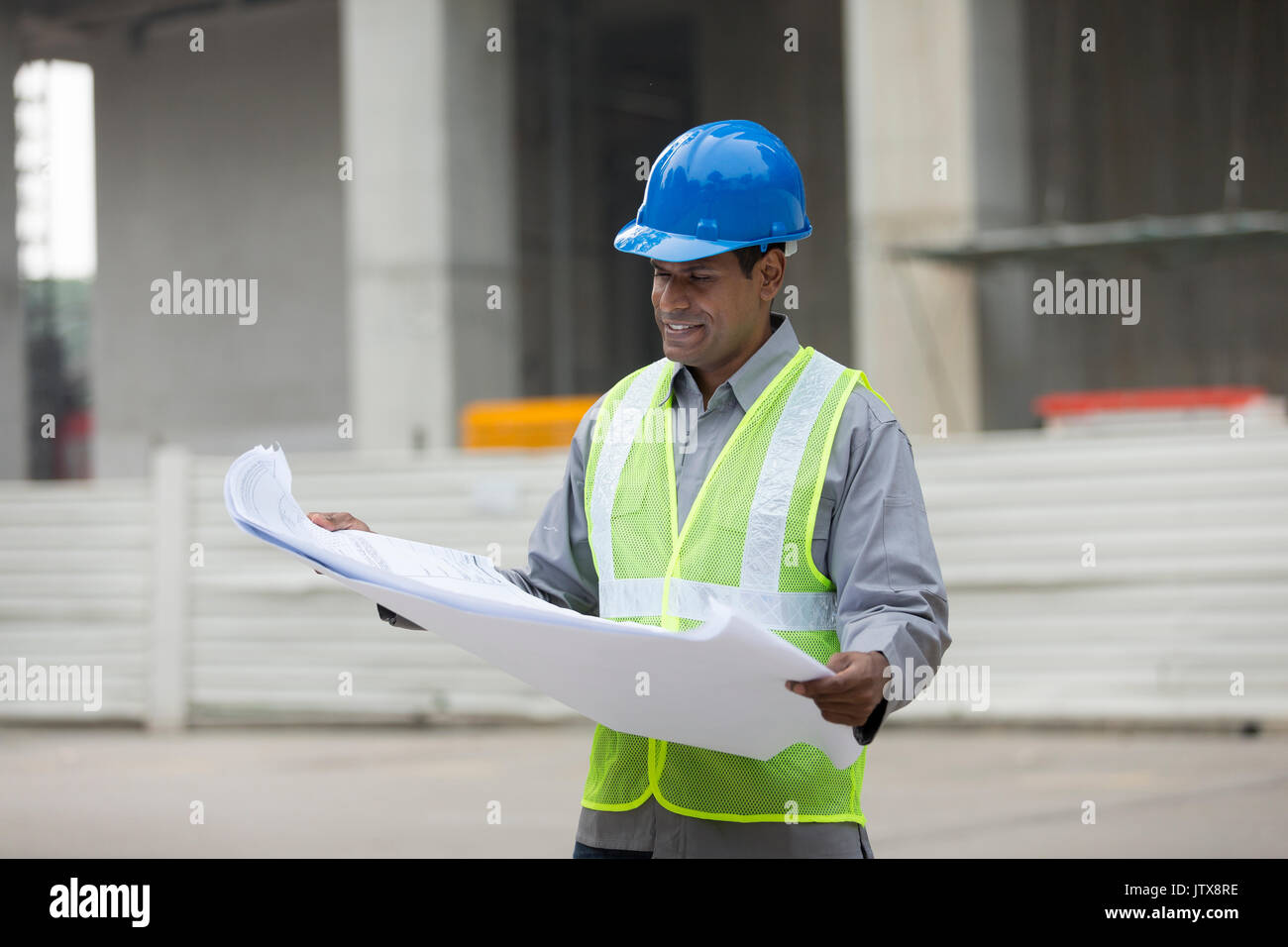 Professional indian male architect checking house blueprint stock indian construction manager or architect checking the blueprint plans at a building site stock malvernweather Choice Image