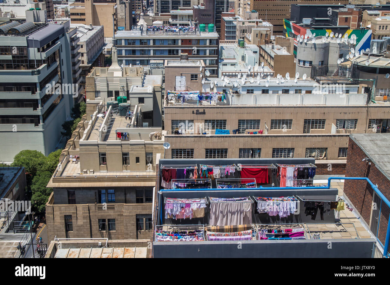 Laundry of inner city dwellers hung out on a sunny day on a myriad washing lines on apartment building rooftops in central Johannesburg - Stock Image