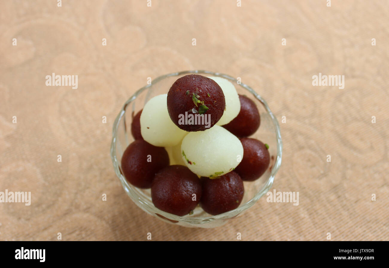 Gulab Jamun and Rasgulla lying over one another in a glass bowl - Stock Image