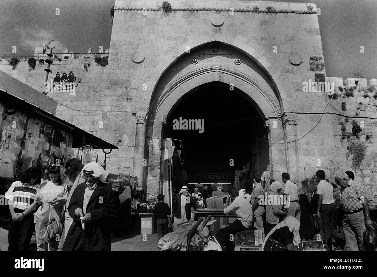 Damascus Gate pictured 1990 ( Bab el-Amud), (Sha'ar Sh'khem) is one of the main entrances to the Old City of Jerusalem. The gate was re-built in 1537 by the Sultan Suleiman the Magnificent, ruler of the Ottoman Empire. Beneath the current gate an earlier gate can be seen dating to the time of the Roman Empire. The Arab-Israeli conflict is a struggle over land, history and religion. It's also a dispute over who owns Jerusalem and its holy sites.  To Jews, Jerusalem, Yerushalayim, is the historical capital of the biblical Israelites. To Muslims, Al Quds or Bayt al-Maqdis is the third holiest si - Stock Image