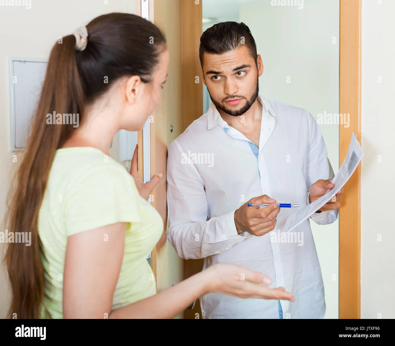 Businessman trying to collect money from housewife at  door Stock Photo