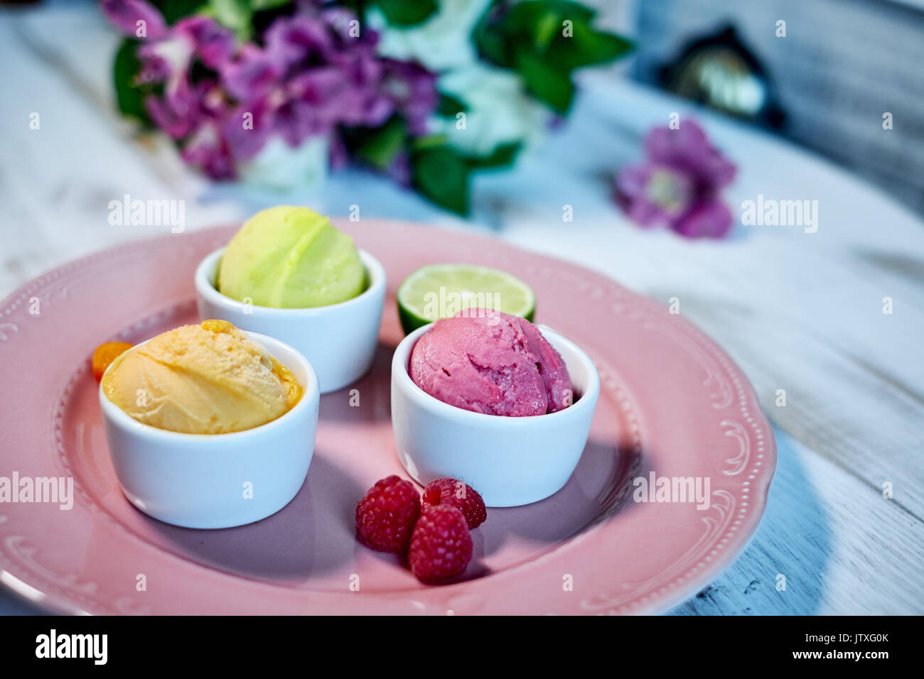 Selection of gourmet flavours of Italian ice cream in vibrant colors served in individual porcelain cups on an old Stock Photo