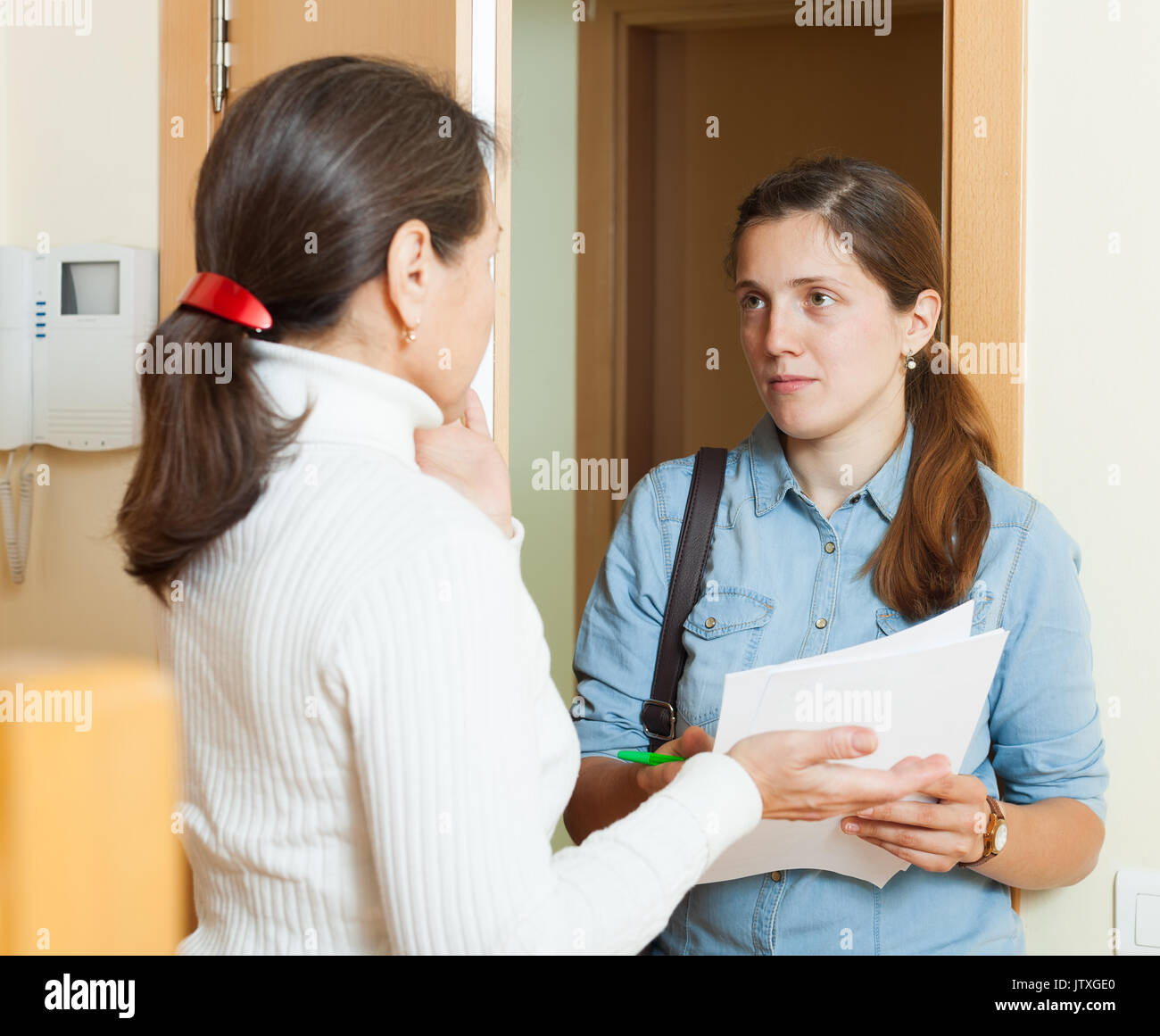 Female collector is trying to get the arrears from woman at home door - Stock Image