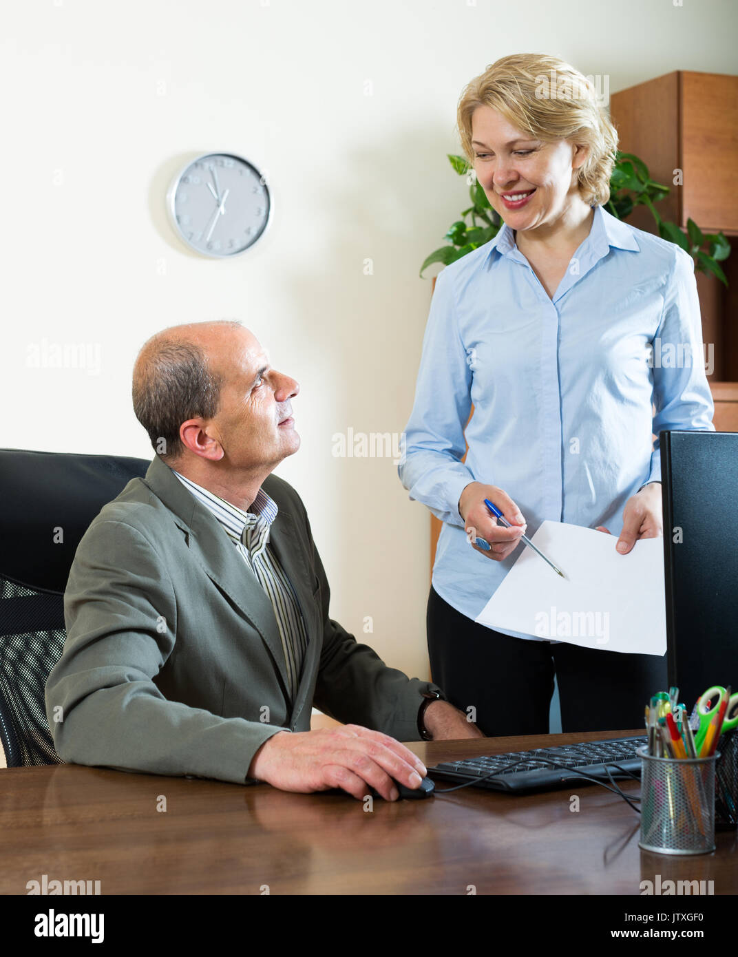aged chief talking with smiling mature female secretary in office
