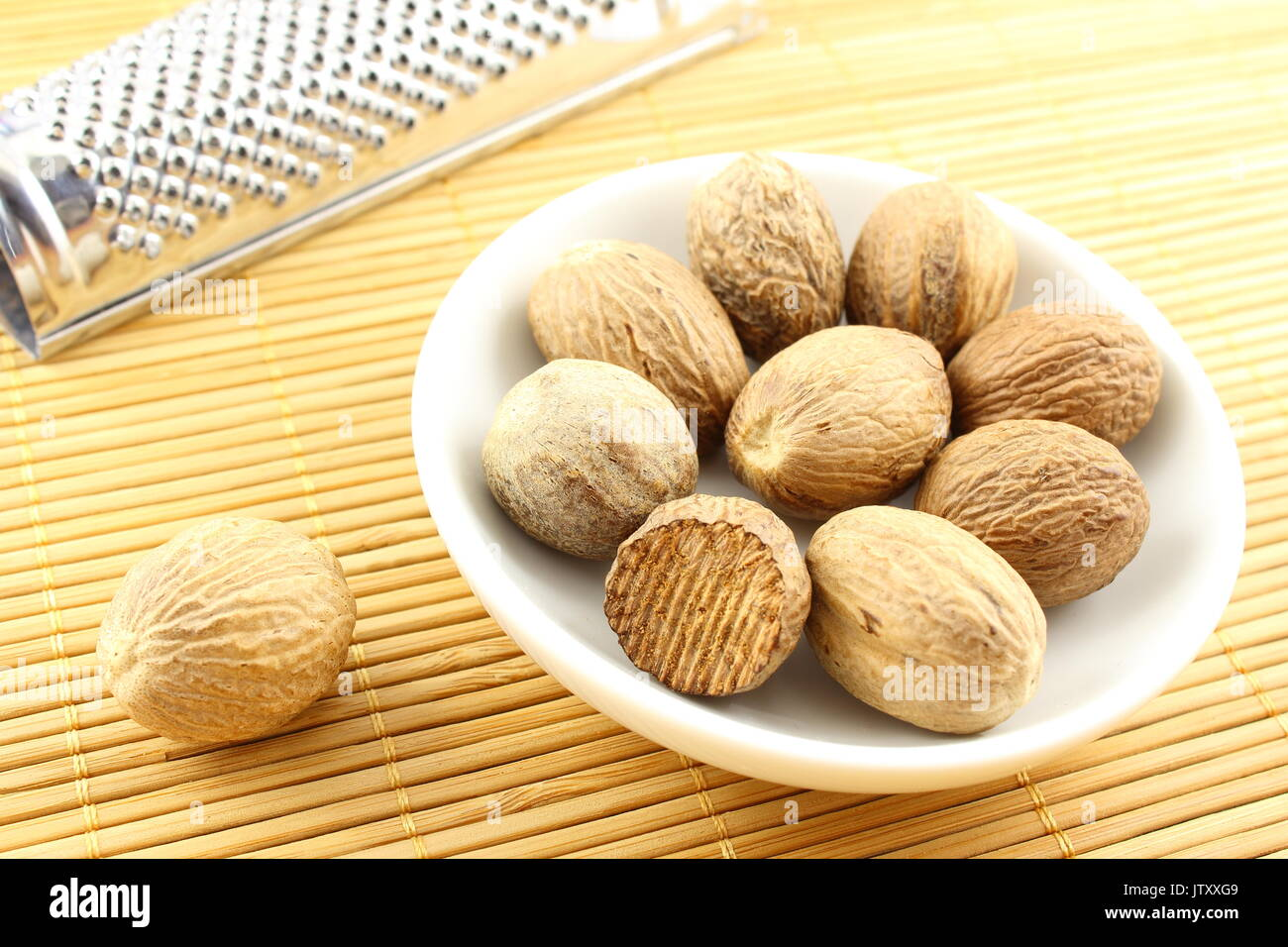 composition of nutmeg seeds in a small white bowl - Stock Image