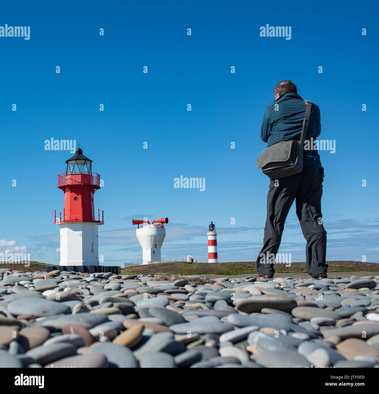 Photographer taking photos of two lighthouses and fog horn in a row at Point of Ayre - Stock Image