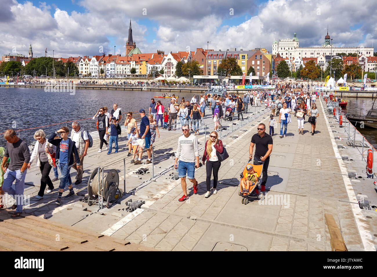 Szczecin, Poland - August 06, 2017: Visitors cross Oder river with military floating bridge during final of The Tall Ships Races 2017. - Stock Image