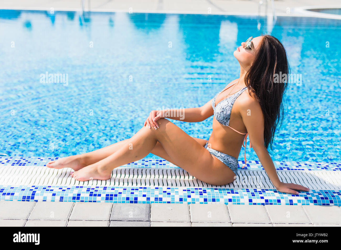 Beautiful young woman sitting by swimming-pool vocation. - Stock Image