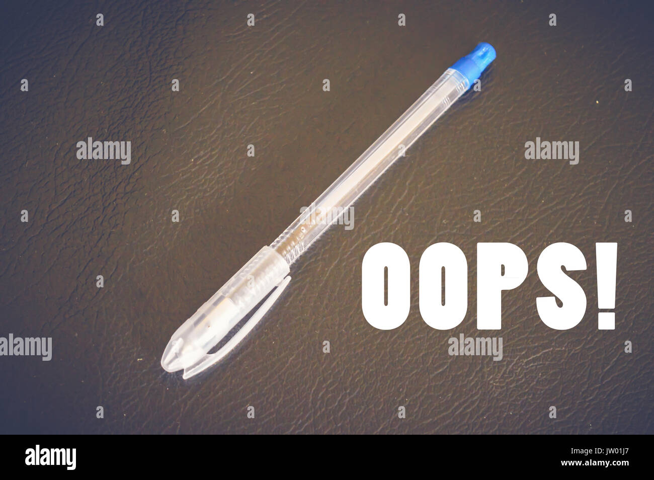 Oops! with pen on wooden table - Stock Image