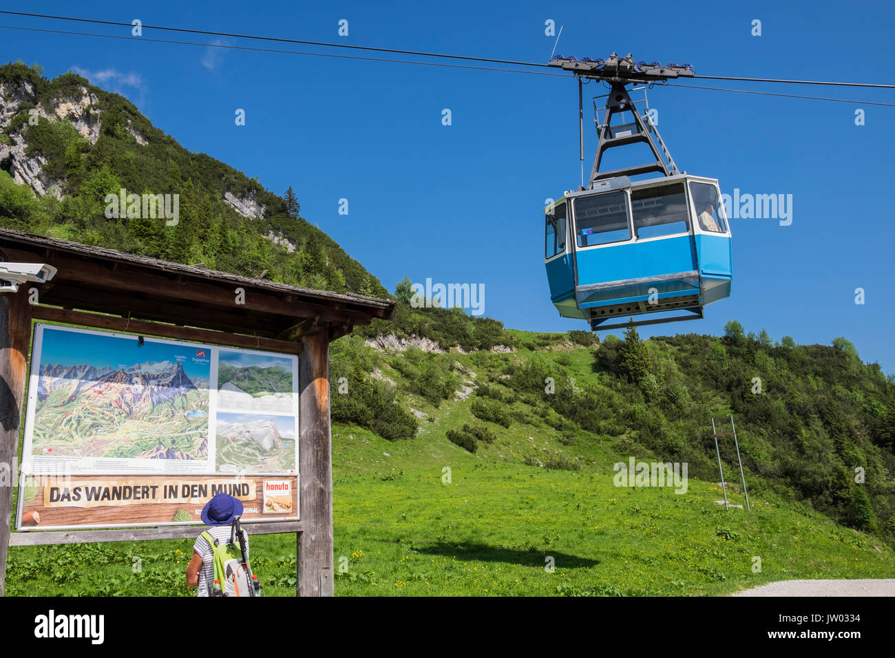 Woman walker reading information panel as Hochalmbahn cable car cabin is coming down the mountain, Hochalm, Kreuzeck, Stock Photo